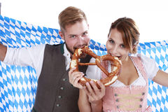 Bavarian couple in traditional costume with beer and brezel. And checkered flag royalty free stock photography