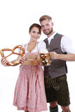 Bavarian couple in traditional costume with beer and brezel Royalty Free Stock Images