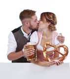 Bavarian couple in traditional costume with beer and brezel Royalty Free Stock Photos