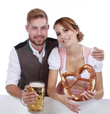 Bavarian couple in traditional costume with beer and brezel Stock Images