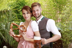 Bavarian couple in traditional costume with beer and brezel Stock Photography