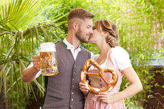 Bavarian couple in traditional costume with beer and brezel Royalty Free Stock Image