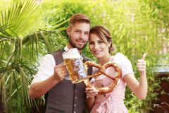 Bavarian couple in traditional costume with beer and brezel Stock Photo
