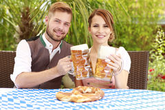 Bavarian couple in traditional costume with beer and brezel Royalty Free Stock Photography