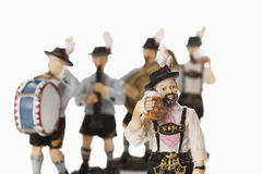 Bavarian figurine drinking beer with figurines playing music in background Stock Image