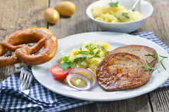 Bavarian food. Fried slices of sausage with pieces of pig spleen (so called 'Milzwurst') served with potato salad and a pretzel Stock Photo