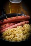 Bavarian fried sausages on sauerkraut Stock Images