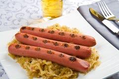 Bavarian fried sausages on sauerkraut Stock Photos