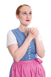 Bavarian girl in a dirndl praying isolated on white Royalty Free Stock Photo