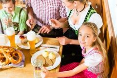 Bavarian girl with family in restaurant. Bavarian girl wearing dirndl and eating with family in traditional restaurant royalty free stock photo