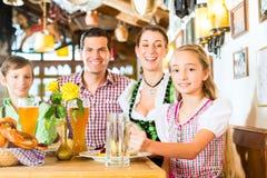 Bavarian girl with family in restaurant. Bavarian girl wearing dirndl and eating with family in traditional restaurant royalty free stock image