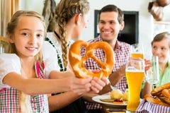 Bavarian girl with family in restaurant. Bavarian girl wearing dirndl and eating with family in traditional restaurant royalty free stock images