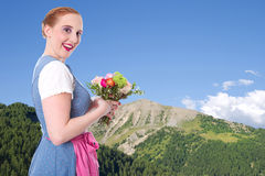 Bavarian girl with flowers and blue sky with mountains as backgr Stock Images