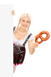 Bavarian girl holding a pretzel behind blank panel Stock Photo