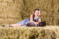 Bavarian girl playing with cat on hayloft Stock Image