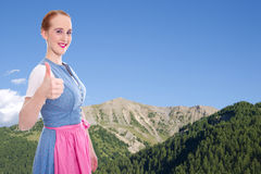 Bavarian girl with thumb up and blue sky as background Royalty Free Stock Photos