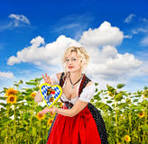 Bavarian girl in tracht dress dirndl in sunflower field. Over cloudy blue sky royalty free stock images
