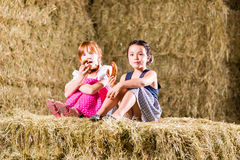 Bavarian girls sitting on hayloft - pretzels Royalty Free Stock Photography