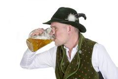 Bavarian man drinking from a mug of beer Royalty Free Stock Photo