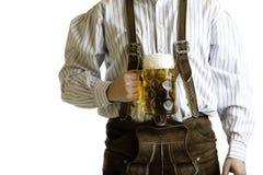 Bavarian man hold beer stein at Oktoberfest. Bavarian man dressed with original leather trousers holds an Oktoberfest beer stein into the camera Royalty Free Stock Photos