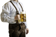 Bavarian man hold beer stein at Oktoberfest. Bavarian man dressed with original leather trousers holds an Oktoberfest beer stein into the camera Stock Photography