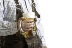 Bavarian man hold beer stein at Oktoberfest. Bavarian man dressed with original leather trousers holds an Oktoberfest beer stein into the camera Stock Photos