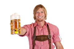 Bavarian man holds oktoberfest beer stein. Happy smiling man with leather trousers (lederhose) holds oktoberfest beer stein. Isolated on white background Stock Photos