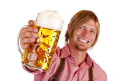 Bavarian man holds oktoberfest beer stein. Happy smiling man with leather trousers (lederhose) holds oktoberfest beer stein. Isolated on white background Royalty Free Stock Photography