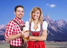 Bavarian man with leather pants and blonde woman with dirndl celebrating the oktoberfest. Bavarian men with leather pants and blonde women with dirndl royalty free stock image