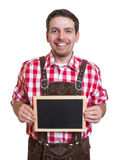 Bavarian man with leather pants and chalk board Royalty Free Stock Image