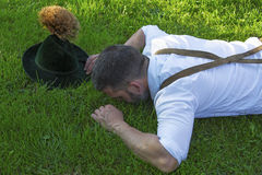 Bavarian man lying on the grass Stock Image