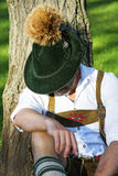Bavarian man sitting by a tree and sleeps Stock Image