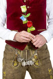 Bavarian man in traditional clothes holding a plastic flower Royalty Free Stock Photography