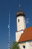 Bavarian Maypole with church Stock Image