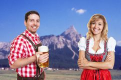 Bavarian man with beer mug and blonde woman with dirndl celebrating the oktoberfest. Bavarian men with beer mug and blonde women with dirndl celebrating the royalty free stock photo
