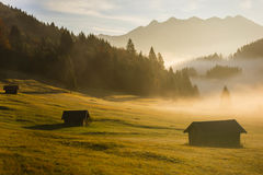 Bavarian morning. A foggy morning in the Bavarian mountains. The huts were covered by the rays of an early sunrise Royalty Free Stock Photos