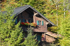 Bavarian mountain hut standing between trees on the mountainside Royalty Free Stock Photos