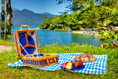 Bavarian outdoor picnic. Bavarian striped picnic cloth with basket and food on it Stock Photography