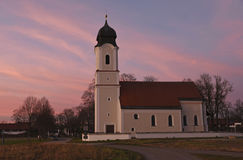Bavarian pilgrimage chapel and pink sunset sky Stock Photos