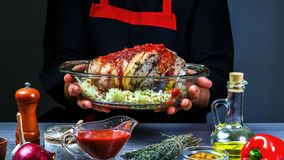 Bavarian pork knuckle cooking with sauerkraut, sharp chili sauce and beer in baking pan by chef hands, steps on black background stock photo