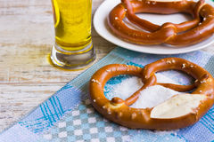 Bavarian pretzel and a glass of lager. A glass of lager and two Bavarian pretzel on a wooden table Stock Photo