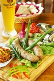 Bavarian sausage-grill. With fresh vegetables and solyanka on wooden board Stock Photo