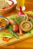Bavarian sausage-grill. With fresh vegetables and solyanka on wooden board Royalty Free Stock Image