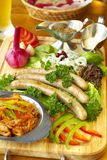 Bavarian sausage-grill. With fresh vegetables and solyanka on wooden board Stock Photography