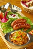Bavarian sausage-grill. With fresh vegetables and solyanka on wooden board Royalty Free Stock Photography