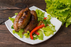 Bavarian sausages cooked on the grill. Wooden table Stock Image