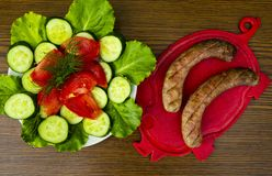 Bavarian sausages on a cutting board with vegetables. Cucumber, tomato, green salad. View from above. Place for text royalty free stock photos