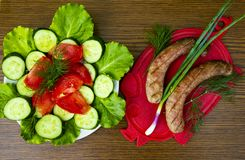 Bavarian sausages on a cutting board with vegetables stock image