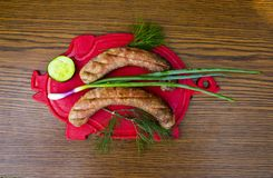 Bavarian sausages on a cutting board with vegetables. Cucumber, tomato, green salad. View from above. Place for text stock photography