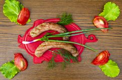 Bavarian sausages on a cutting board with vegetables. Cucumber, tomato, green salad. View from above. Place for text royalty free stock photo